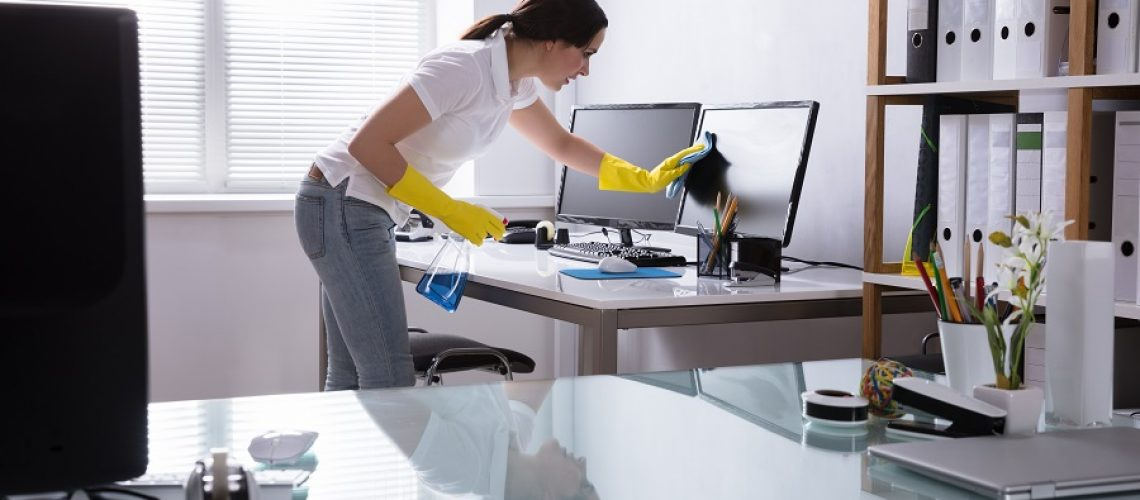 Young Woman Cleaning Computer With Rag In Office